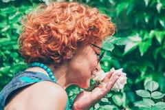 Sentir mûr de femme a monté dans le jardin Photographie stock libre de droits