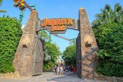 Sentosa, Singapura-ABRIL 12,2016: A porta grande na frente do tema de Jurassic Park no estúdio universal Singapura foto de stock