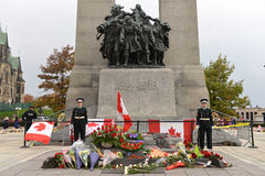 Sentries at the Cenotaph in Ottawa. Ceremonial guards stand at attention while mourners pay respect at the Ottawa Cenotaph where guard Nathan Cirillo was shot 3 royalty free stock image