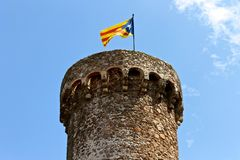 Senyera estelada, Tossa de Mar, Catalonia, Spain. A Senyera estelada, the unofficial flag typically flown by Catalan independence supporters, waving on the tower Royalty Free Stock Photography