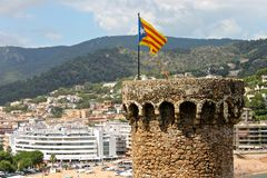 Senyera estelada, Tossa de Mar, Catalonia, Spain. A Senyera estelada, the unofficial flag typically flown by Catalan independence supporters, waving on the tower Royalty Free Stock Images