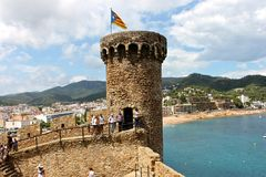 Senyera estelada, Tossa de Mar, Catalonia, Spain. A Senyera estelada, the unofficial flag typically flown by Catalan independence supporters, waving on the tower Stock Photo