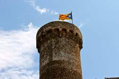 Senyera estelada, Tossa de Mar, Catalonia, Spain. A Senyera estelada, the unofficial flag typically flown by Catalan independence supporters, waving on the tower Royalty Free Stock Photos