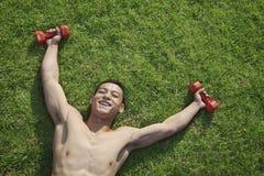 Senza camicia, sorridendo, uomo muscolare che si trova nell'erba con le teste di legno a Pechino, vista da sopra Fotografia Stock