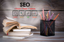 SEO Business Concept. Stack of books and pencils on the wooden table. Royalty Free Stock Photos