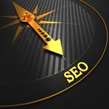 SEO. Internet Concept. SEO - Internet Concept. Golden Compass Needle on a Black Field Pointing to the SEO Word Royalty Free Stock Images