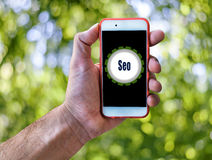 Seo Marketing Concept Hand holding mobile on abstract green background. Close Royalty Free Stock Photography