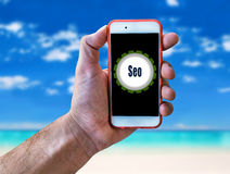 Seo Marketing Concept Hand holding mobile on beach background. Close Royalty Free Stock Images