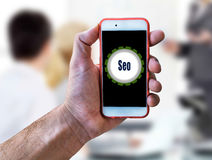 Seo Marketing Concept Hand holding mobile. Close Royalty Free Stock Images