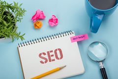SEO, online concept. Notepad with message, pen, coffee cup and flower. Office supplies on desk table top view Stock Photo