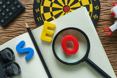SEO optimization concept with pencil, dartboard, robot, calculat Royalty Free Stock Photo