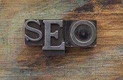 SEO - search engine optimization. SEO (search engine optimization) acronym - vintage leterpress metal type blocks on a grunge painted wood royalty free stock image