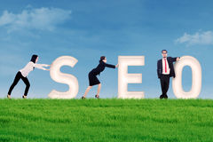 SEO - Search Engine Optimization. Business people pushing SEO letter on grass under blue sky Royalty Free Stock Photography