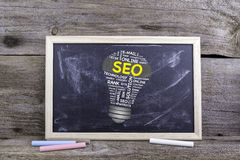 SEO (search engine optimization) bulb word cloud. Chalk board on. A wooden table Royalty Free Stock Images