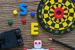 SEO search engine optimization concept with pencil, dartboard, m. Agnifying glass, robot and alphabets abbreviation SEO on wood table Stock Image