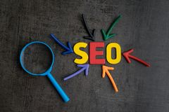 SEO, Search Engine Optimization ranking concept, magnifying glass with arrows pointing to alphabets abbreviation. SEO at the center of cement wall chalkboard stock image