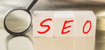 SEO search engine optimization text wooden cubes and magnifying glass on a Golden background. Idea  vision  strategy  analysis