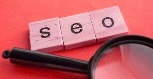 SEO search engine optimization text wooden cubes and magnifying glass on a red background. Idea  vision  strategy  analysis