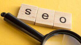 SEO search engine optimization text wooden cubes and magnifying glass on a yellow background. Idea  vision  strategy  analysis