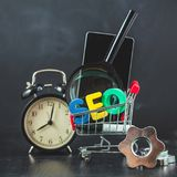SEO Search-Maschinenoptimierungskonzept färbte die Buchstaben von SEO mit Uhr und an vergrößerte, Smartphone, Gänge in einem Korb Lizenzfreies Stockbild