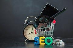 SEO Search-Maschinenoptimierungskonzept färbte die Buchstaben von SEO mit Uhr und an vergrößerte, Smartphone, Gänge in einem Korb Lizenzfreie Stockfotografie