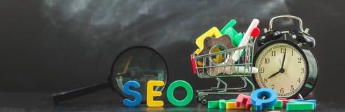 SEO Search-Maschinenoptimierungskonzept färbte die Buchstaben von SEO mit Uhr und vergrößerte, Smartphone, Gänge in einem Korb au Lizenzfreie Stockfotografie
