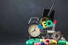 SEO Search-Maschinenoptimierungskonzept färbte die Buchstaben von SEO mit Uhr und vergrößerte, Smartphone, Gänge in einem Korb au Lizenzfreies Stockbild
