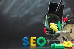 SEO Search-Maschinenoptimierungskonzept färbte die Buchstaben von SEO mit Uhr und vergrößerte, Smartphone, Gänge in einem Korb au Lizenzfreie Stockbilder
