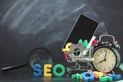 SEO Search-Maschinenoptimierungskonzept färbte die Buchstaben von SEO mit Uhr und vergrößerte, Smartphone, Gänge in einem Korb au Lizenzfreies Stockfoto