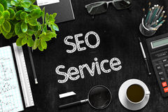 SEO Service on Black Chalkboard. 3D Rendering. Royalty Free Stock Photos