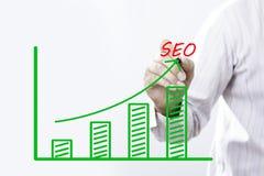 SEO-tekst met hand van jong zakenmanpunt op virtuele grafiek Stock Afbeelding