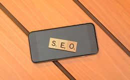 SEO theme, wooden text box with smart phone stock image
