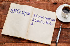 SEO tips in a notebook with coffee. SEO (search engine optimization) tips (great content and quality links) in an old notebook with a cup of coffee stock images