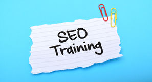 SEO Training written on paper with blue background.  Stock Image
