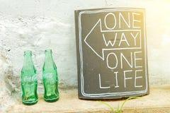 SEOEL, KOREA - AUGUSTUS 09, 2015: Twee lege flessen van Coca-Cola naast ceramische plaat met woorden Stock Afbeelding