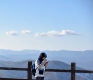 Seoel, KOREA - JANUARI 29, 2017: Vrouw die de berg bij de winter van pijler bekijken Gekleed in zwart jasje met kap Royalty-vrije Stock Foto's
