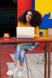 Señora africana joven hermosa que se sienta en la cafetería con el ordenador portátil Fotografía de archivo libre de regalías