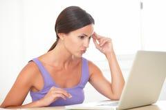 Señora cansada que practica surf el web en el ordenador Fotos de archivo libres de regalías