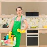 Señora de la limpieza que señala el shooting de la botella del aerosol de la limpieza feliz y la sonrisa Imágenes de archivo libres de regalías
