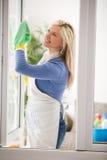 Señora de la limpieza que señala el shooting de la botella del aerosol de la limpieza feliz y la sonrisa Imagenes de archivo