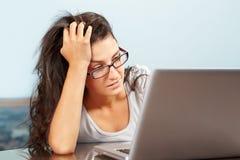 Señora deprimida delante de la computadora portátil Foto de archivo