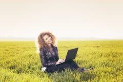 Señora hermosa con su ordenador portátil en hierba Imagenes de archivo
