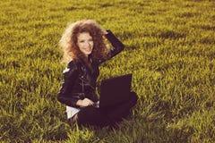 Señora hermosa con su ordenador portátil en hierba Imagen de archivo