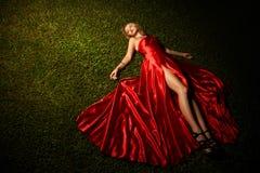 Señora hermosa In Red Dress Lying en hierba Imagenes de archivo