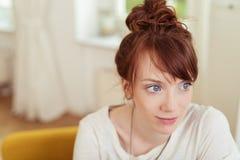 Señora joven en la sala de estar que mira en distancia Fotos de archivo libres de regalías