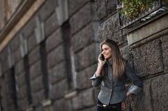 Señora joven feliz que habla en el teléfono móvil Fotos de archivo libres de regalías