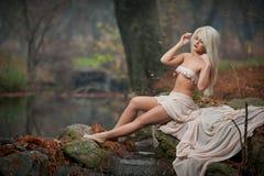 Señora joven preciosa que se sienta cerca del río en bosque encantado Blonde sensual con la ropa blanca que presenta provocativo  Fotografía de archivo libre de regalías