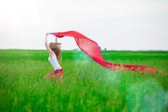 Señora joven que corre con el tejido en campo verde Imágenes de archivo libres de regalías