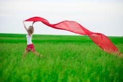 Señora joven que corre con el tejido en campo verde Mujer con la bufanda Fotos de archivo libres de regalías