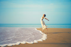 Señora joven que salta en la playa Imagen de archivo